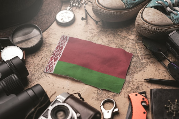 Bandeira da bielorrússia entre acessórios do viajante no antigo mapa vintage. conceito de destino turístico.