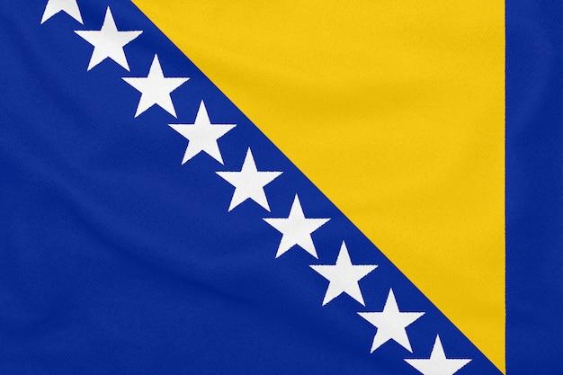 Bandeira da bósnia e herzegovina em tecido texturizado. símbolo patriótico
