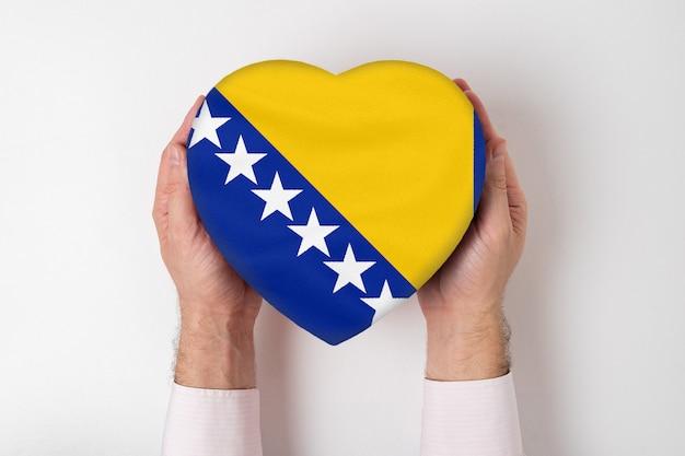 Bandeira da bósnia e herzegovina em uma caixa em forma de coração nas mãos de um homem.