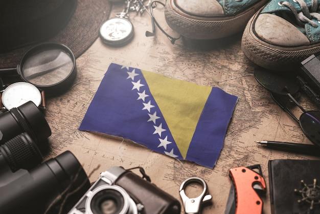 Bandeira da bósnia e herzegovina entre acessórios do viajante no antigo mapa vintage. conceito de destino turístico.