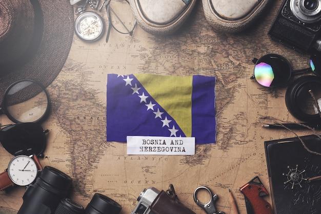 Bandeira da bósnia e herzegovina entre acessórios do viajante no antigo mapa vintage. tiro aéreo