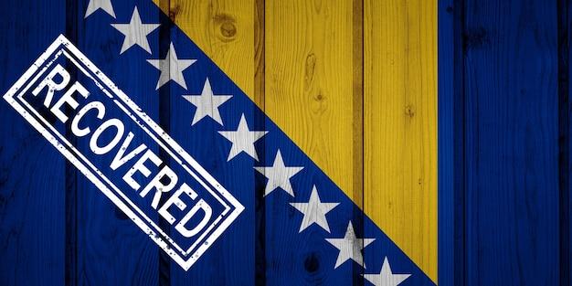 Bandeira da bósnia e herzegovina que sobreviveu ou se recuperou das infecções da epidemia do vírus corona ou coronavírus. bandeira do grunge com selo recuperado