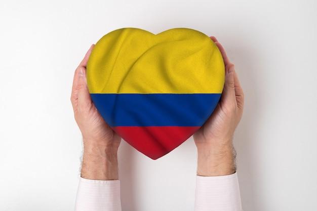 Bandeira da colômbia em uma caixa em forma de coração nas mãos masculinas.