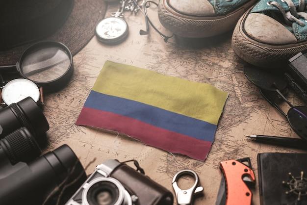 Bandeira da colômbia entre acessórios do viajante no antigo mapa vintage. conceito de destino turístico.