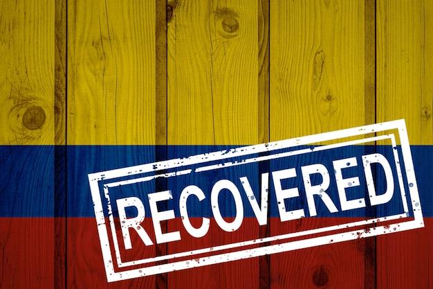Bandeira da colômbia que sobreviveu ou se recuperou das infecções da epidemia do vírus corona ou coronavírus. bandeira do grunge com selo recuperado
