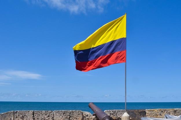 Bandeira da colômbia tremulando e canhões na muralha da cidade murada no centro histórico de cartagena.