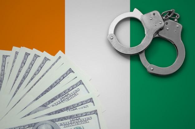 Bandeira da costa do marfim com algemas e um maço de dólares. o conceito de operações bancárias ilegais em moeda americana