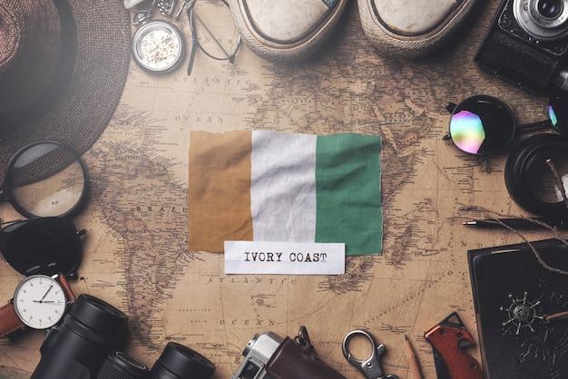 Bandeira da costa do marfim entre acessórios do viajante no antigo mapa vintage. tiro aéreo