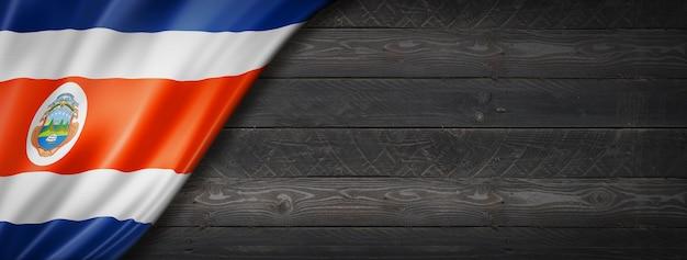 Bandeira da costa rica na parede de madeira preta. banner panorâmico horizontal.