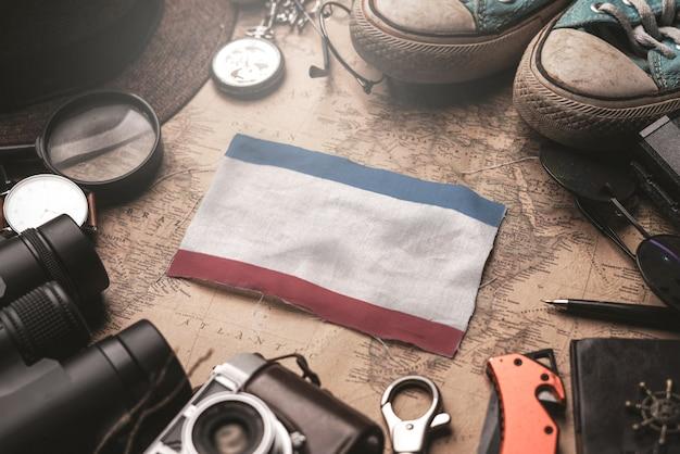Bandeira da crimeia entre acessórios do viajante no mapa antigo do vintage. conceito de destino turístico.