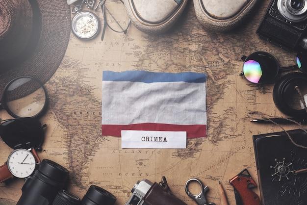 Bandeira da crimeia entre acessórios do viajante no mapa antigo do vintage. tiro aéreo