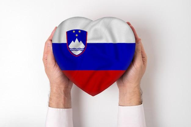 Bandeira da eslovénia em uma caixa em forma de coração nas mãos masculinas.