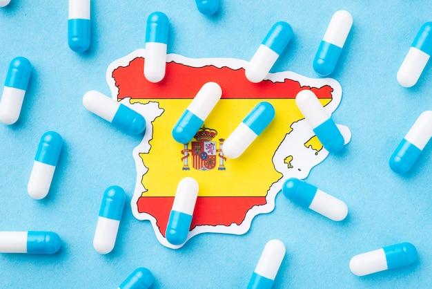 Bandeira da espanha com muitas cápsulas no topo, simbolizando o mau estado de saúde dos cidadãos