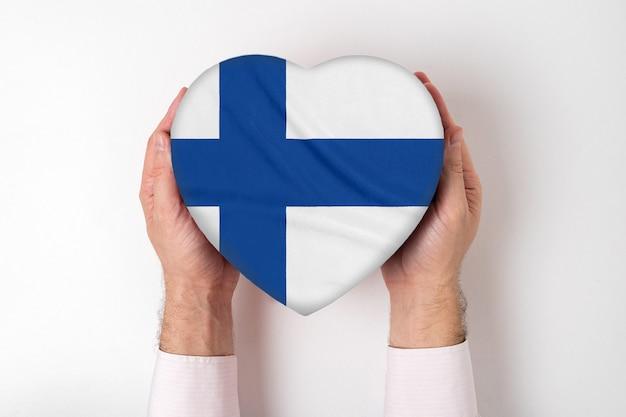 Bandeira da finlândia em uma caixa em forma de coração nas mãos masculinas. fundo branco