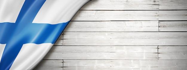 Bandeira da finlândia na velha parede branca. faixa panorâmica horizontal.