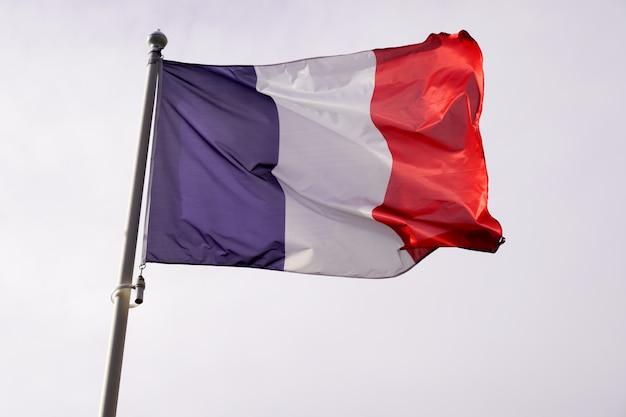 Bandeira da frança acenando sobre céu azul branco vermelho cor