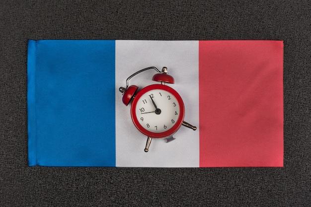 Bandeira da frança e despertador vintage, close-up. hora de aprender francês