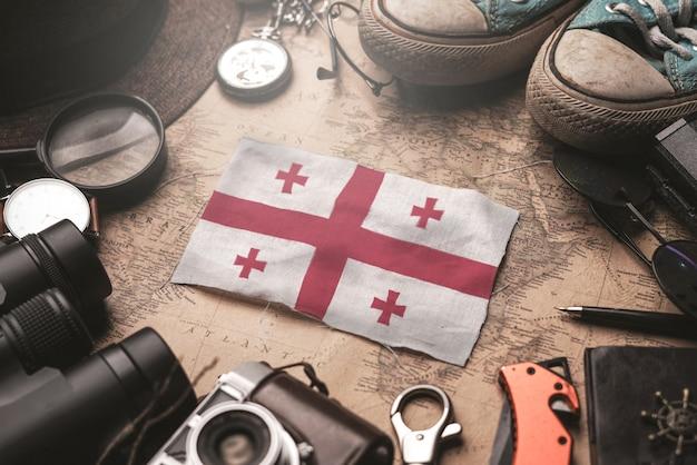 Bandeira da geórgia entre acessórios do viajante no mapa antigo do vintage. conceito de destino turístico.