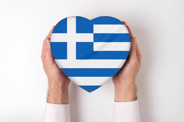 Bandeira da grécia em uma caixa em forma de coração nas mãos masculinas.