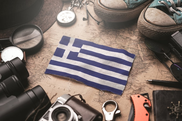 Bandeira da grécia entre os acessórios do viajante no antigo mapa vintage. conceito de destino turístico.