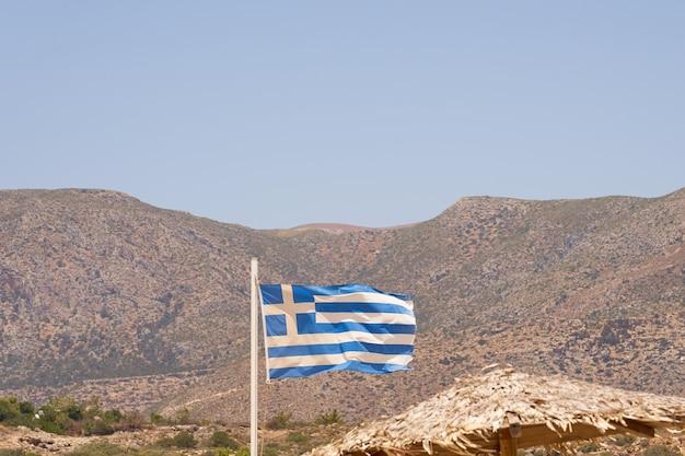 Bandeira da grécia na praia com montanhas ao fundo.