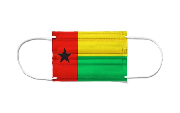 Bandeira da guiné-bissau com máscara cirúrgica descartável. superfície branca isolada