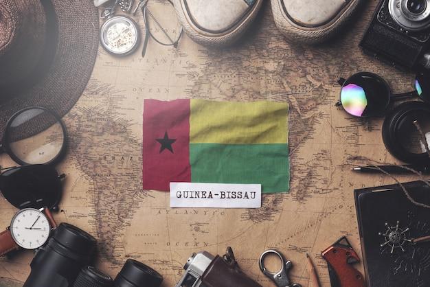 Bandeira da guiné-bissau entre acessórios do viajante no antigo mapa vintage. tiro aéreo