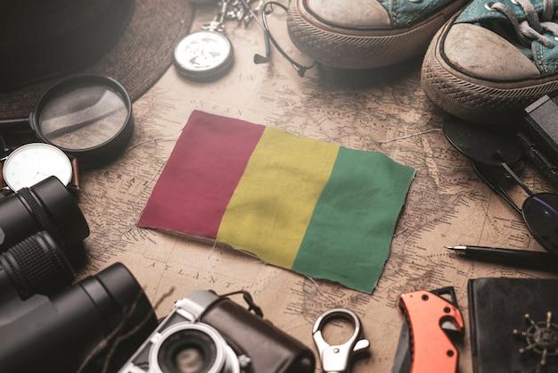 Bandeira da guiné entre acessórios do viajante no antigo mapa vintage. conceito de destino turístico.