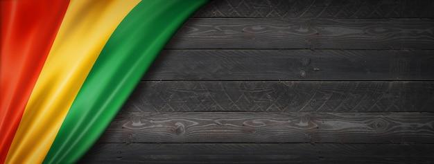 Bandeira da guiné na parede de madeira preta