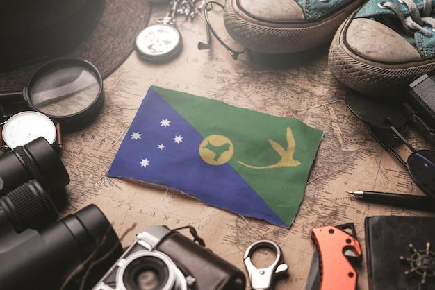 Bandeira da ilha christmas entre acessórios do viajante no mapa antigo do vintage. conceito de destino turístico.