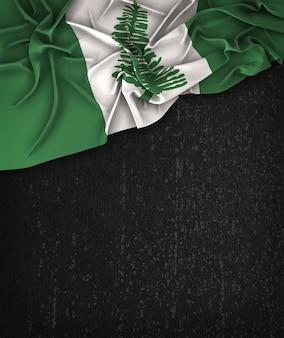 Bandeira da ilha de norfolk vintage em um quadro preto do grunge com espaço para o texto