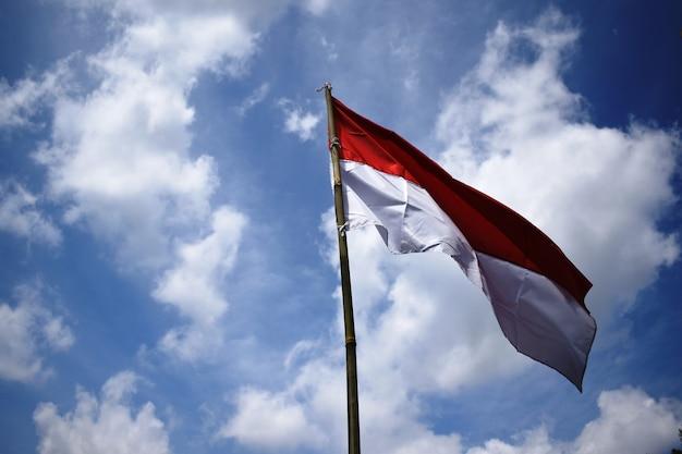 Bandeira da indonésia sob o céu azul levantando bandeira vermelha e branca