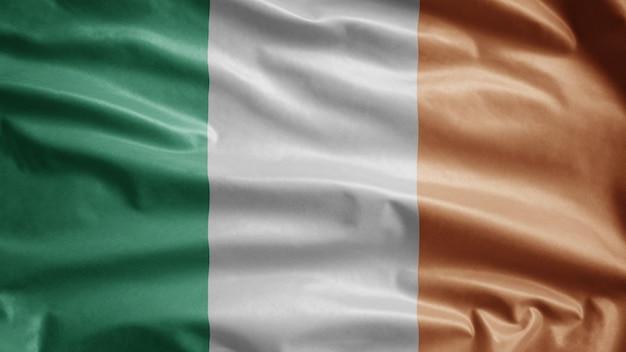 Bandeira da irlanda balançando ao vento. bandeira irlandesa soprando, seda macia e suave.
