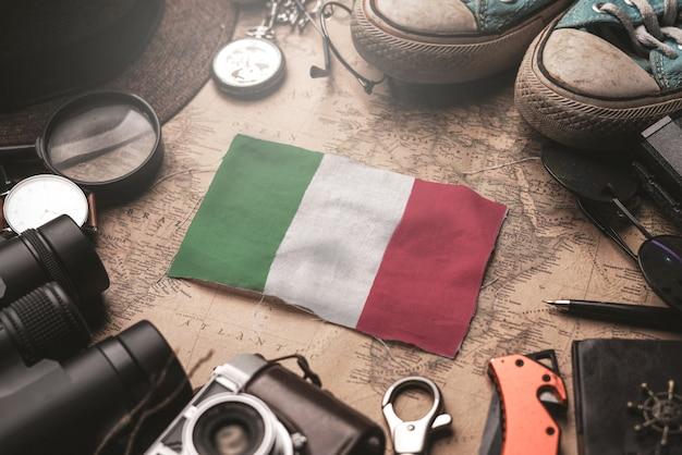 Bandeira da itália entre os acessórios do viajante no antigo mapa vintage. conceito de destino turístico.