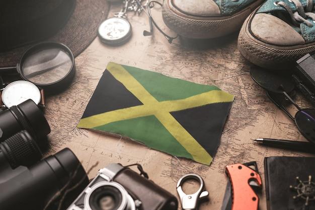 Bandeira da jamaica entre acessórios do viajante no antigo mapa vintage. conceito de destino turístico.