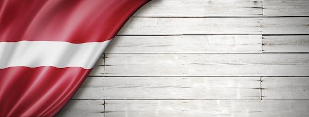 Bandeira da letônia na velha parede branca.