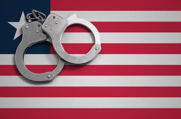 Bandeira da libéria e algemas da polícia. o conceito de crime e ofensas no país
