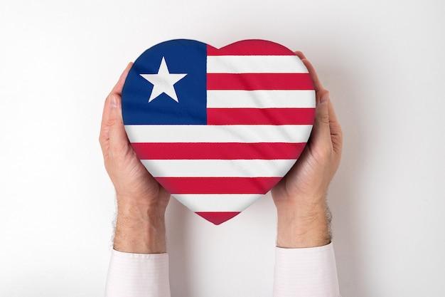 Bandeira da libéria em uma caixa em forma de coração nas mãos masculinas. fundo branco