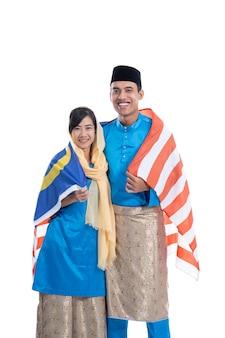 Bandeira da malásia. casal vestindo roupas tradicionais muçulmanas feliz sobre fundo branco