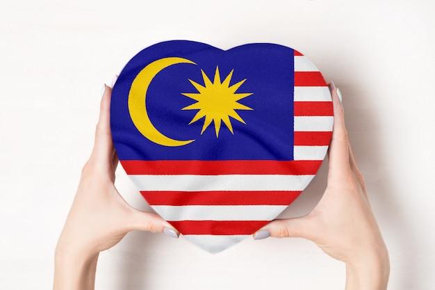 Bandeira da malásia em uma caixa em forma de coração nas mãos femininas.