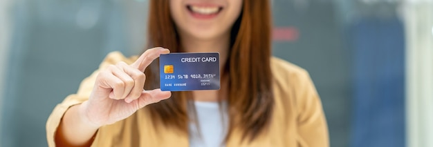 Bandeira da mulher asiática segurando e apresentando o cartão de crédito para compras on-line em loja de departamento