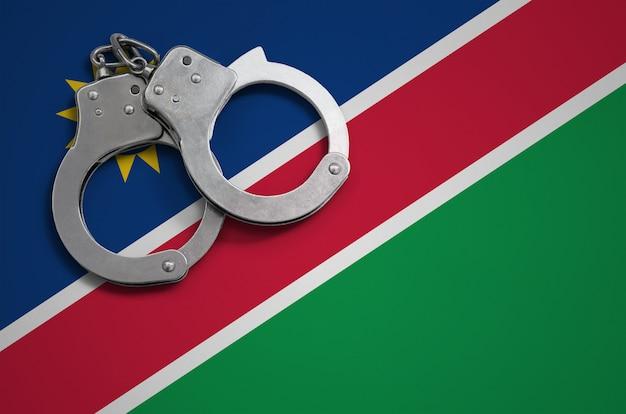 Bandeira da namíbia e algemas da polícia. o conceito de crime e ofensas no país
