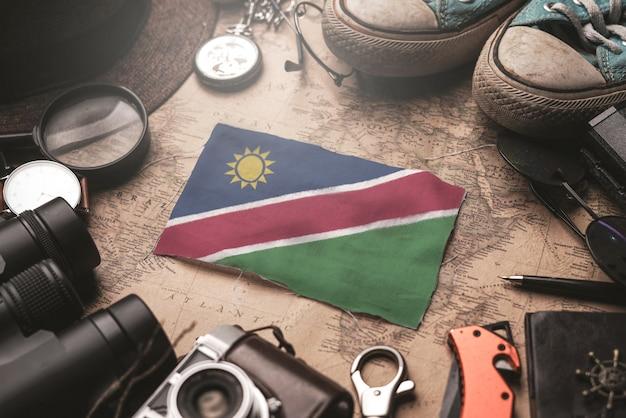 Bandeira da namíbia entre acessórios do viajante no antigo mapa vintage. conceito de destino turístico.