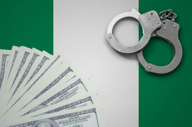 Bandeira da nigéria com algemas e um pacote de dólares. o conceito de operações bancárias ilegais em moeda americana