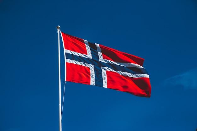 Bandeira da noruega contra o céu azul. o vento sopra contra o céu azul sem nuvens.
