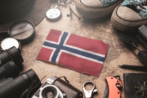 Bandeira da noruega entre acessórios do viajante no mapa antigo do vintage. conceito de destino turístico.