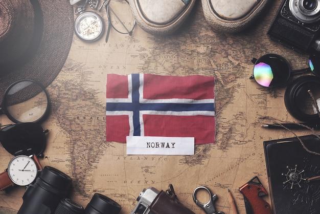 Bandeira da noruega entre acessórios do viajante no mapa antigo do vintage. tiro aéreo