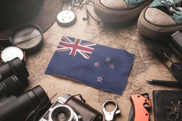 Bandeira da nova zelândia entre acessórios do viajante no antigo mapa vintage. conceito de destino turístico.