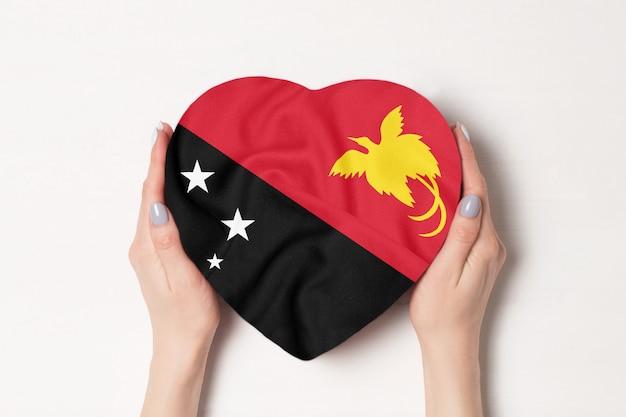 Bandeira da papua-nova guiné em uma caixa em forma de coração em uma mão feminina.