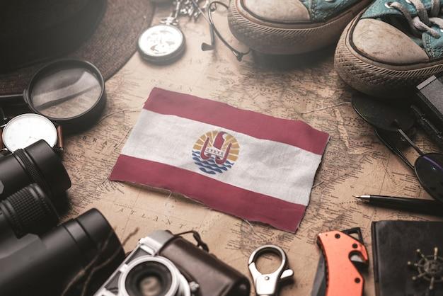 Bandeira da polinésia francesa entre os acessórios do viajante no antigo mapa vintage. conceito de destino turístico.